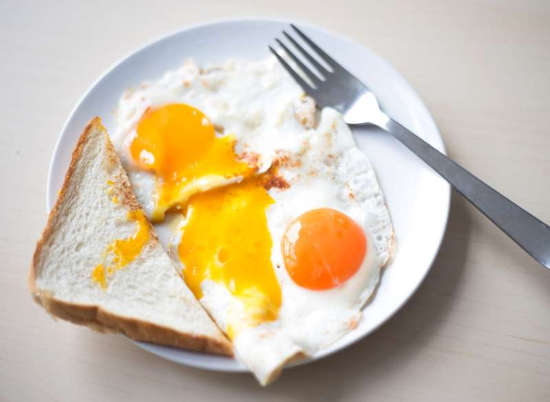 a plate of food with a fork and knife: Egg yolks will range in color—from pale yellow to deep orange to even a bright red—based on a hen's diet. Because free-range hens often eat more pigmented, nutritious foods that range from insects to grasses, eggs from these chickens often have richer-colored yolks. On the other hand, conventional, grain-fed chickens will produce lighter yellow yolks. As for those red yolks we mentioned? One chef—Dan Barber, executive chef of New York-based Blue Hill restaurants—worked with Cornell University researchers to develop a feed blend high in red peppers that allowed hens to produce strawberry-colored yolks.As for the difference in nutrients between yolk colors? The protein and fat counts will often remain the same regardless of yolk color, but there can be up to a 100-fold increase in micronutrient value of certain antioxidant carotenoids like lutein and beta-carotene in yolks fed a more nutrient-dense diet (like in pasture-raised hens), according to a 2010 study published in the Journal of the Science of Food and Agriculture. Rich, dark yolks will contain more of these potent antioxidants: compounds which mop up harmful toxins that promote inflammation and fat storage. Other studies have indicated that the same healthy diet that produces richer-colored yolks results in eggs with higher levels of heart-healthy omega-3s and less cholesterol.